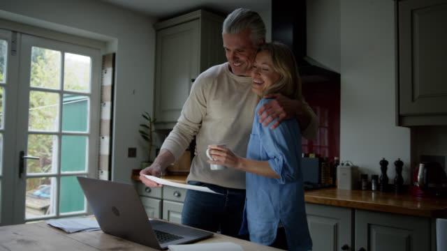 vídeos y material grabado en eventos de stock de pareja caucásica en casa discutiendo un proyecto mirando un documento mientras apunta a la pantalla del ordenador portátil - pareja madura