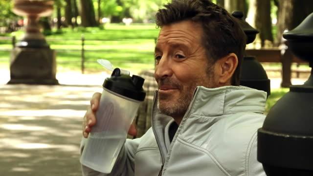 vidéos et rushes de caucasian couple drinking water bottle in park - embrasser sur la bouche