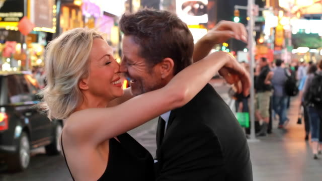 caucasian couple hugging in busy city, new york, new york, united states - zungenkuss stock-videos und b-roll-filmmaterial