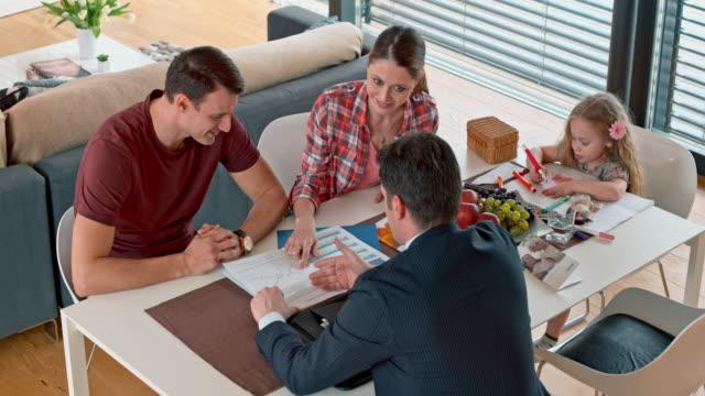 Kaukasische paar in vergadering met persoonlijke bankier in hun huis