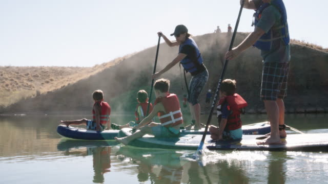 a caucasian couple paddles stand-up paddleboards with children on a lake along a desert-cliff shoreline under a clear blue sky - salvataggio video stock e b–roll