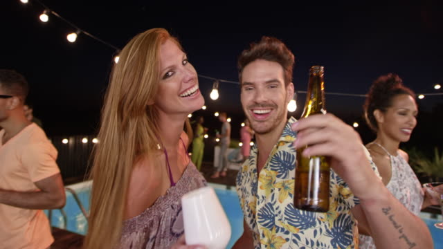kaukasische paar posieren für das smartphone video auf einer party am pool am abend - wickelkleid stock-videos und b-roll-filmmaterial