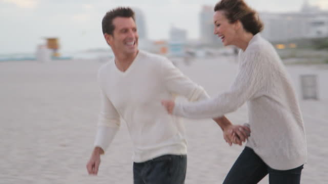 caucasian couple running on the beach - mature couple stock videos and b-roll footage