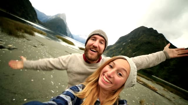 Caucasian couple take selfie portrait with mountain landscape