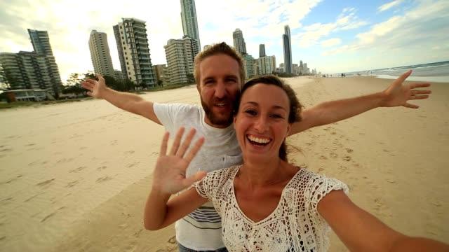 Caucasian couple taking selfie portrait on Surfers paradise beach