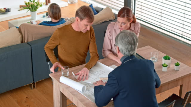 Caucasian couple talking to a male architect in their home