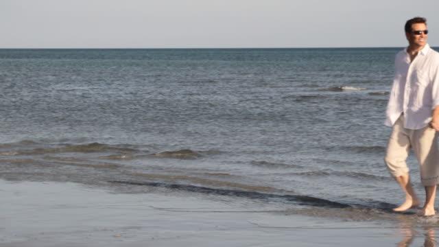 caucasian couple walking on beach and hugging - mittellanges haar stock-videos und b-roll-filmmaterial