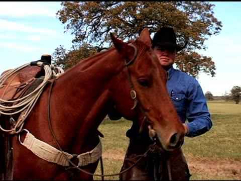 stockvideo's en b-roll-footage met caucasian cowboy dismounts brown horse on texas ranch - alleen één mid volwassen man