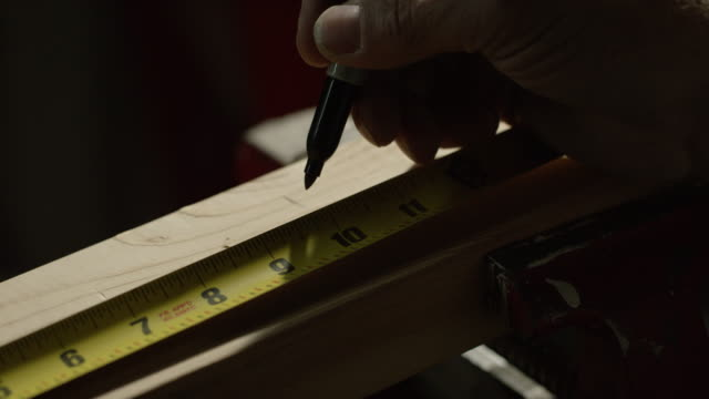 a caucasian craftsman marks a measurement on a wooden board with a marker and a tape measure - bricolage video stock e b–roll