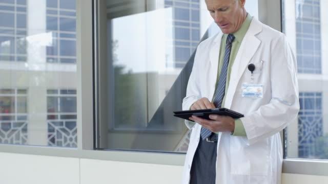 caucasian doctor leaning on window using digital tablet - skjorta och slips bildbanksvideor och videomaterial från bakom kulisserna