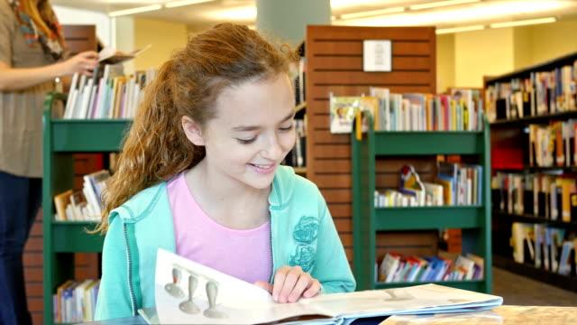 vídeos de stock e filmes b-roll de de escola primária casa escola caucasiano menina lê um livro ilustrado no local da biblioteca - arquivista