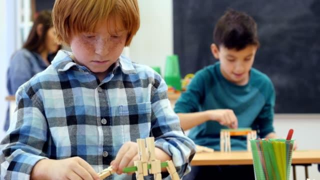 vídeos y material grabado en eventos de stock de estudiantes de primaria caucásico trabaja en proyecto de ingeniería - artesanía