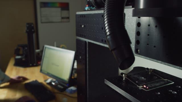 ein kaukasischer ingenieur in seinen vierzig jahren, der augenschutz trägt, arbeitet auf seinem computer, während ein machender ultra-fast laser sapphire in einer indoor-fertigungsanlage schneidet - schutzbrille freisteller stock-videos und b-roll-filmmaterial
