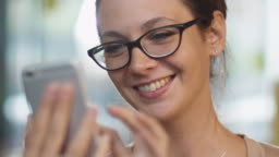 Caucasian Ethnicity Smiling Young Woman using Mobile Phone at Cozy Coffee Shop.