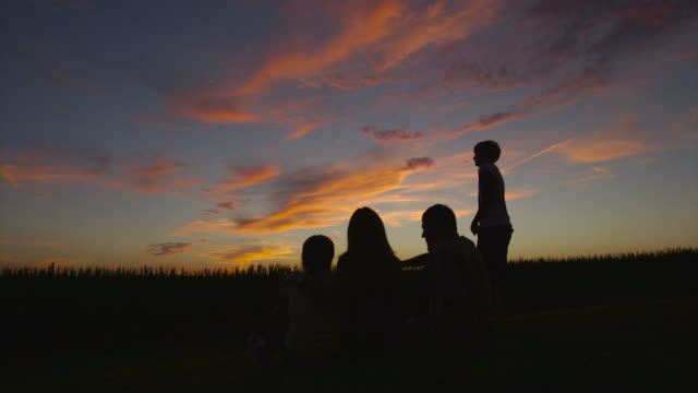 caucasian family admiring sunset - illinois stock-videos und b-roll-filmmaterial