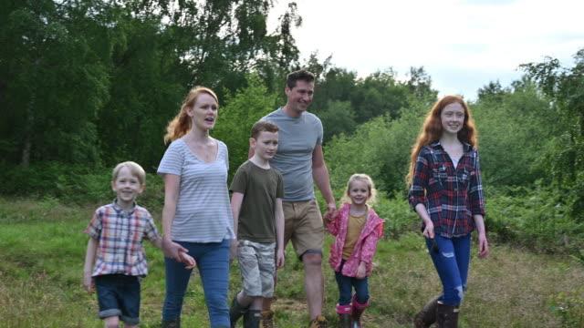 vídeos de stock e filmes b-roll de caucasian family and dog enjoying natural parkland in spring - família com quatro filhos