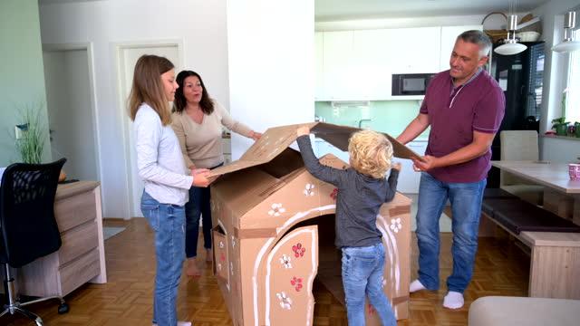kaukasische familie gebäude karton hotel und putting dach auf der oberseite zu hause - spielzeughaus stock-videos und b-roll-filmmaterial