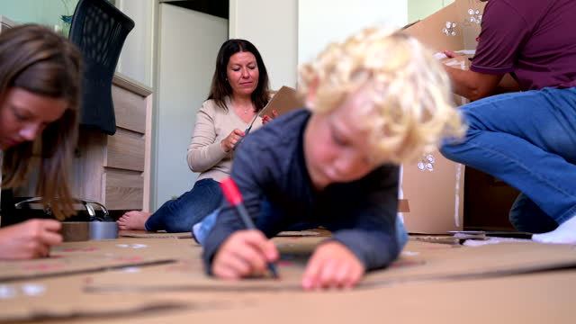 caucasian family building cardboard hotel at home - diy stock videos & royalty-free footage