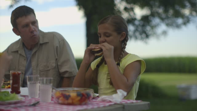 Caucasian family eating at barbecue