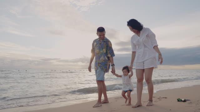 kaukasisk familj som håller händer och går längs stranden vid solnedgången - gå tillsammans bildbanksvideor och videomaterial från bakom kulisserna