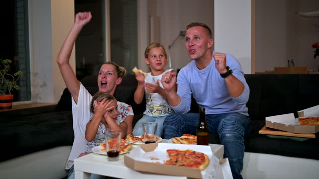 caucasian family sitting on a sofa eating pizza and watching tv - fan enthusiast stock videos & royalty-free footage