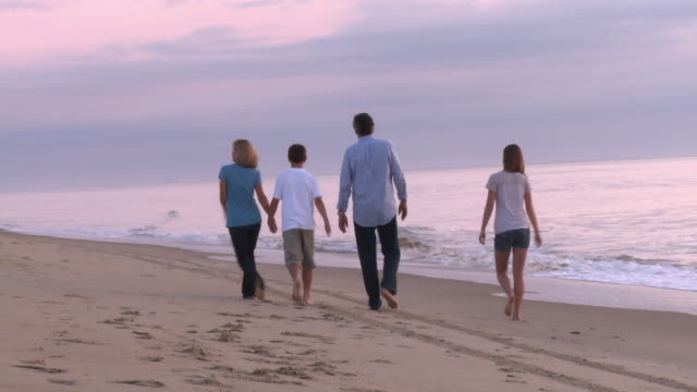 vidéos et rushes de caucasian family walking away from camera along beach at sunrise - empreinte de pas