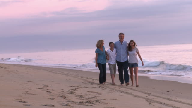 Caucasian family walking toward camera along beach at sunrise