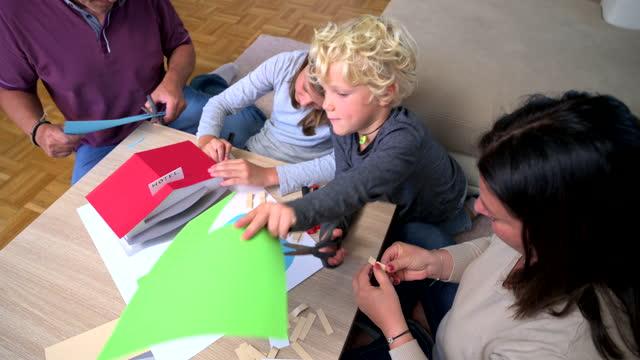 kaukasische familie mit sohn und tochter machen papier modell zu hause - spielzeughaus stock-videos und b-roll-filmmaterial