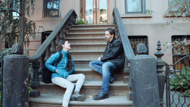 Caucasian father and daughter talking on urban front stoop