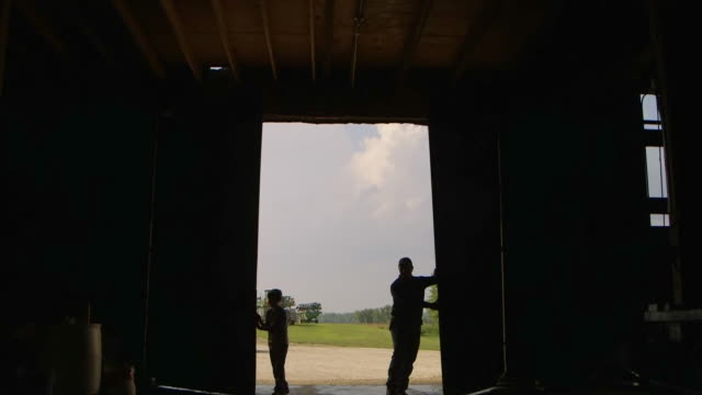 vídeos de stock e filmes b-roll de caucasian father and son opening barn door for truck - missouri