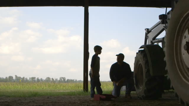 Caucasian father explaining tractor repair to son