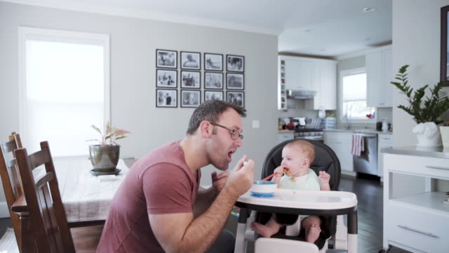 vidéos et rushes de a caucasian father feeding his 6 month old baby boy in a high chair in the kitchen while his wife watches - 6 11 mois