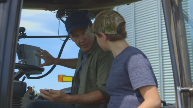 caucasian father teaching son to drive tractor - tractor stock videos & royalty-free footage