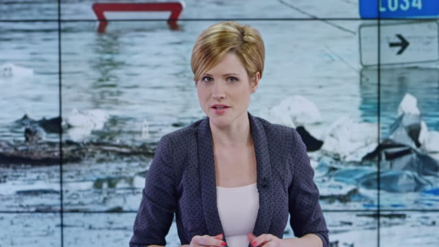 LD Caucasian female anchor presenting the news on recent flooding