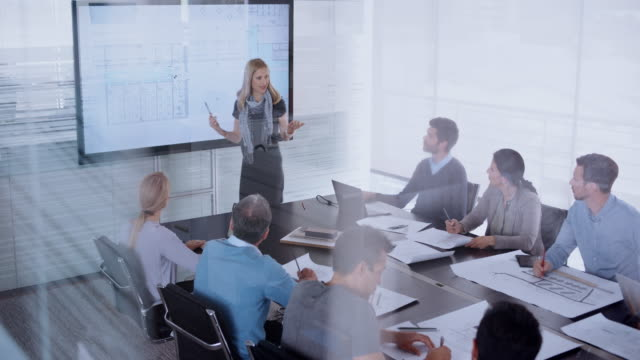 caucasian female architect giving a presentation of the plan details to her colleagues sitting in the conference room - blonde hair stock videos & royalty-free footage