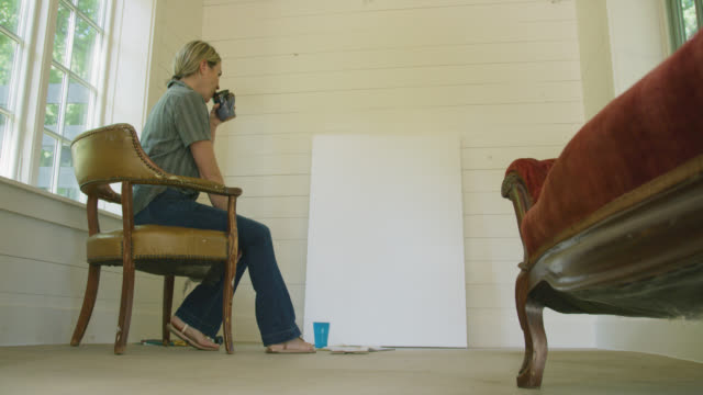 a caucasian female artist in her forties contemplates a large, blank canvas while sitting in a chair and drinking coffee before standing up and adjusting the canvas indoors - canvas stock videos & royalty-free footage