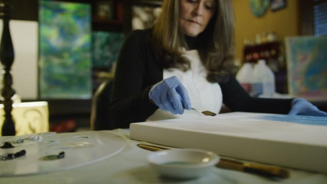 a caucasian female artist in her sixties uses a palette knife to scoop up oil paint and apply it to a canvas in an indoor art studio - oil paint stock videos and b-roll footage