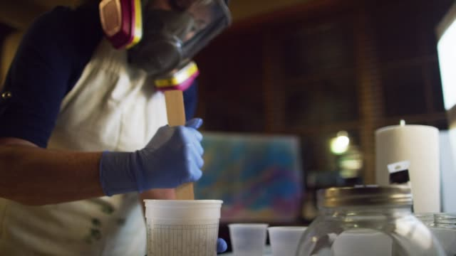 a caucasian female artist wearing safety gloves and a respirator stirs clear epoxy/resin with a wooden craft stick in an indoor art studio - protective mask workwear stock videos and b-roll footage