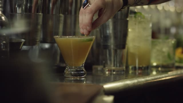 a caucasian female bartender garnishes an alcoholic drink while preparing cocktails at a bar - distillery stock videos and b-roll footage