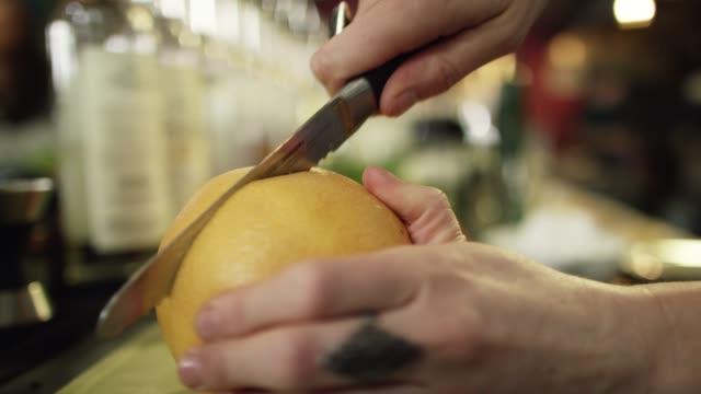 バーで飲み物を準備しながら、白人女性のバーテンダーは、キッチンナイフでグレープフルーツを半分にします - キッチンナイフ点の映像素材/bロール
