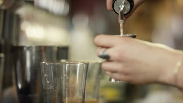 a caucasian female bartender measures alcohol with a shot glass and then pours it into a clear glass with mint leaves while making a cocktail at a bar - distillery stock videos and b-roll footage
