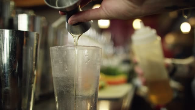 a caucasian female bartender measures simple syrup in a shot glass before pouring it into a clear chilled glass while making a cocktail at a bar - distillery stock videos and b-roll footage