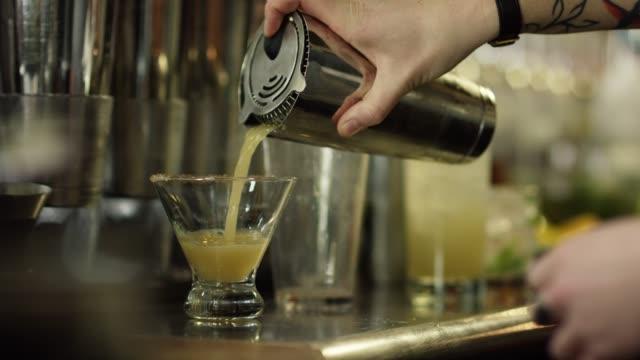 vidéos et rushes de un barman féminin caucasien souches et verse l'alcool d'un shaker dans un verre tout en préparant des cocktails dans un bar - shaker