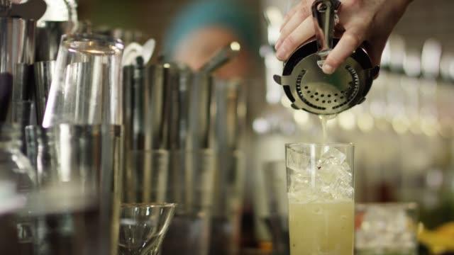 vidéos et rushes de un barman féminin caucasien souches et verse l'alcool d'un shaker dans un verre rempli de glace tout en préparant des cocktails dans un bar - shaker