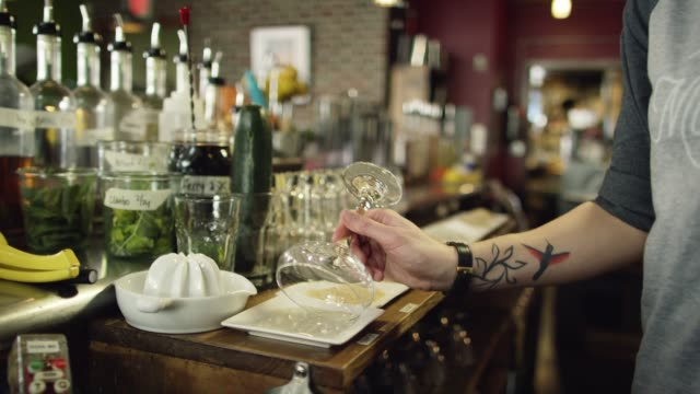 a caucasian female bartender with tattoos dips a martini glass in several different powders to garnish the rim before placing it on the counter while preparing cocktails at a bar - garnish stock videos & royalty-free footage