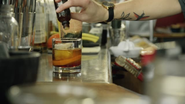 a caucasian female bartender with tattoos pours a few drops of bitters into a cocktail at a bar - distillery stock videos and b-roll footage