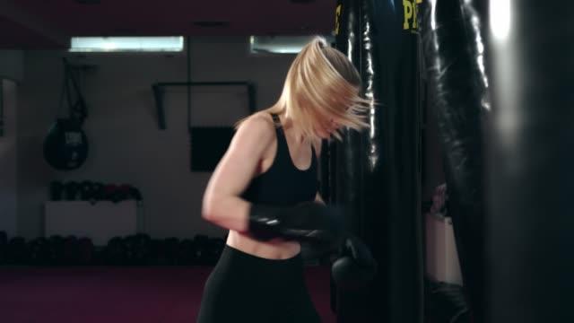 caucasian female boxer punching a punching bag - kickboxing stock videos & royalty-free footage