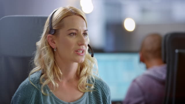 caucasian female call center agent wearing headphones and smiling while talking to a customer - call centre stock videos & royalty-free footage