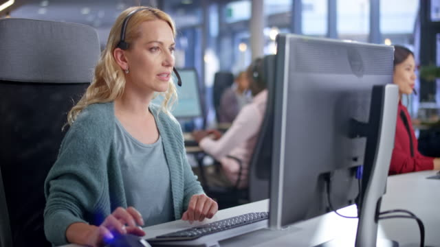 ds caucasian female call centre agent providing customer service at her modern working station - blonde hair stock videos & royalty-free footage