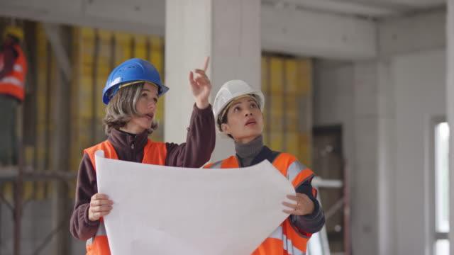 vídeos de stock e filmes b-roll de caucasian female construction engineer talking to an asian female architect at the construction site - arquiteta